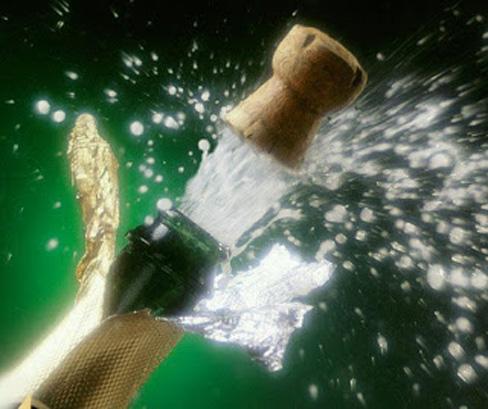 Espumante sendo aberto com barulho e o jorro do vinho