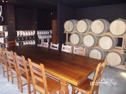 Sala de barricas com mesa para degustações